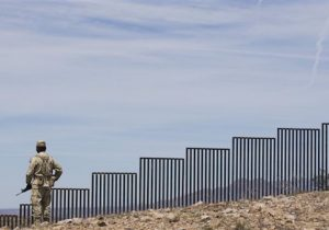 A Mexican soldier patrols along the U.S.-Mexico border wall on the outskirts of Nogales, Mexico