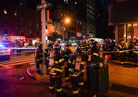 New York City firefighters stand near the site of an explosion in the Chelsea neighborhood of Manhattan, New York