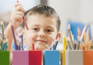 Child picking up a colored pencil (Photo by: Tetra Images/AP Images)