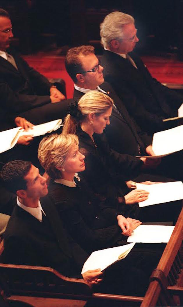 Hillary Rodman Clinton sits with the Puopolo family during a memorial service for Democratic activist Sonia Puopolo. Puopolo's husband Dominic and Dominic, Jr. are at the top. Photo by Wendy Maeda/The Boston Globe via Getty Images