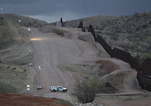A Customs and Border Patrol agent patrols along the international border after sunset in Nogales, Ariz. / AP
