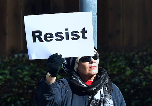 A woman holds a placard reading 'Resist'