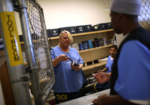 A Valley State Prison inmate hands out supplies to a fellow inmate during a cosmetology class