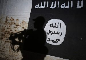 A member of the Iraqi forces walks past a mural bearing the logo of the Islamic State