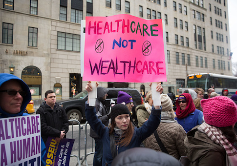 Health care activists lift signage promoting the Affordable Care Act
