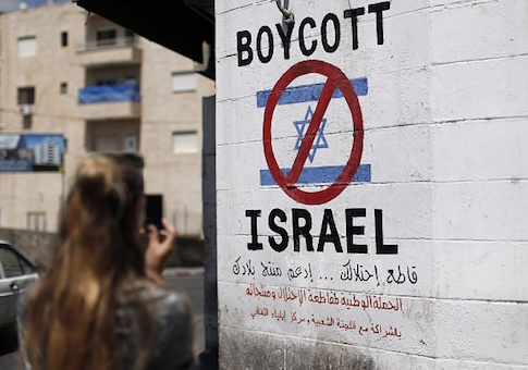 A tourist photographs a sign painted on a wall in the West Bank biblical town of Bethlehem