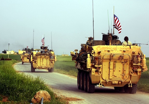 US forces, accompanied by Kurdish People's Protection Units (YPG) fighters, drive their armoured vehicles near the northern Syrian village of Darbasiyah, on the border with Turkey