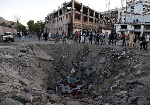 Afghan security forces and residents stand near the crater left by a truck bomb attack in Kabul on May 31