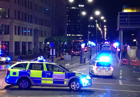 A photograph taken on a mobile phone shows British police cars blocking the entrance to London Bridge, in central London