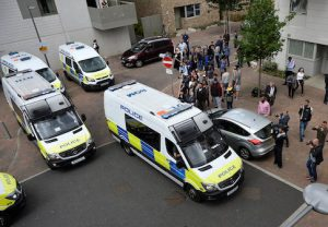 Police vans leave carrying a number of women who were detained after a block of flats was raided in Barking, east London, Britain