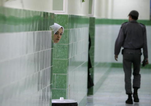 An Iranian inmate peers from behind a wall as a guard walks by at the female section of the infamous Evin jail