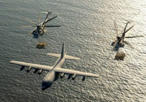 Two U.S. Marine Corps CH-53E Super Stallion helicopters receive fuel from a KC-130 Hercules over the Gulf of Aden