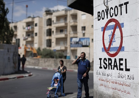 Palestinians walk past a sign painted on a wall calling to boycott Israeli products coming from Jewish settlements