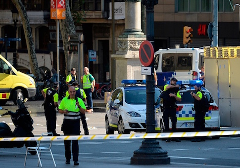Medical staff members and policemen stand in a cordoned off area after a van ploughed into the crowd, injuring several persons on the Rambla in Barcelona