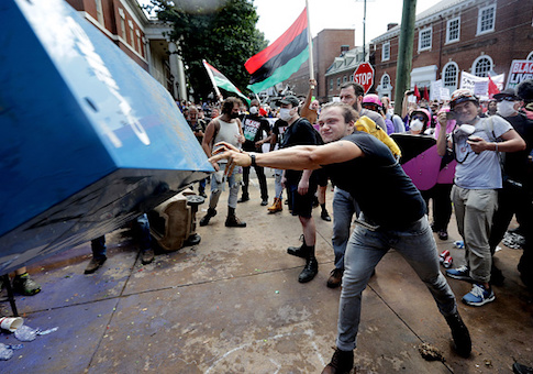 An anti-fascist counter-protester hurls a newspaper box toward white nationalists, neo-Nazis and members of the 'alt-right' during the 'Unite the Right' rally