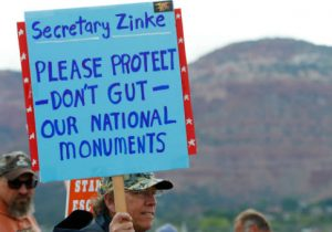 A protester calls on Secretary Zinke not to privatize monuments / Getty