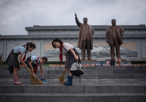 Students clean the steps in front of the statues of late North Korean leaders Kim Il-Sung and Kim Jong-Il at Mansu hill as the country marks 'Victory Day' in Pyongyang on July 27