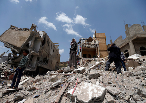 Yemeni men stand on the debris of a house, hit in an air strike on a residential district, in the capital Sanaa