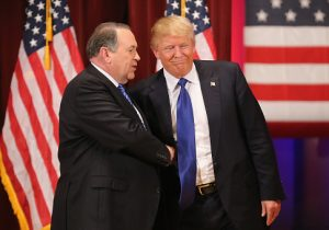 Republican presidential candidate Donald Trump (R) and rival candidate Mike Huckabee shake hands during the rally for veterans at Drake University on January 28, 2016 in Des Moines, Iowa. / Getty Images