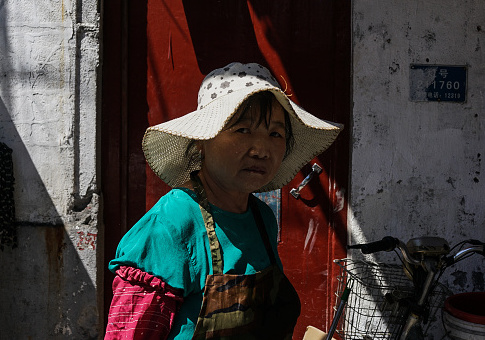 A Chinese construction woman looks on as she walks in the old quarters in Shanghai on September 13, 2017 / Getty Images