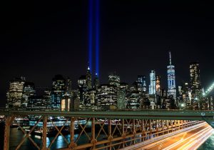 The 'Tribute in Light' rises above the skyline of Lower Manhattan as seen from the Brooklyn Bridge on September 11, 2017
