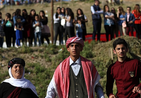 Iraqis Yazidis dance during a ceremony celebrating the Yazidi New Year north east of Mosul