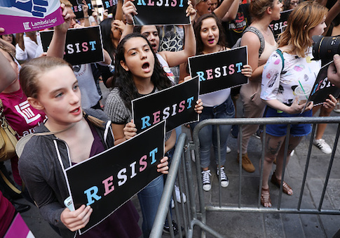 Dozens of protesters gather in Times Square near a military recruitment center to show their anger at President Donald Trump's decision to reinstate a ban on transgender individuals