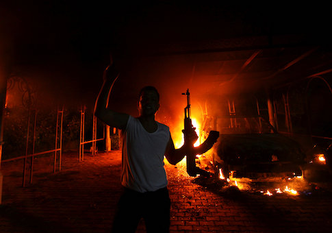 A protester reacts as the U.S. Consulate in Benghazi is seen in flames, September 11, 2012