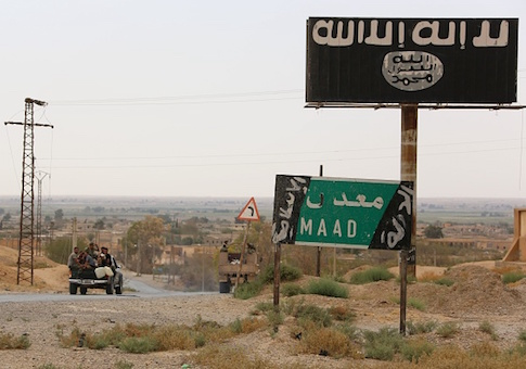 A vehicle drives past a billboard bearing the logo of the Islamic State group in Madan area, in the countryside of Deir Ezzor