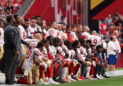 Members of the San Francisco 49ers kneel for the National Anthem / Getty Images