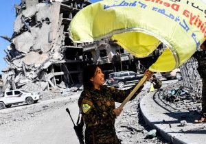 """Rojda Felat, a Syrian Democratic Forces (SDF) commander, waves her group's flag at the iconic Al-Naim square in Raqa on October 17, 2017. US-backed forces said they had taken full control of Raqa from the Islamic State group, defeating the last jihadist holdouts in the de facto Syrian capital of their now-shattered """"caliphate"""". / Getty Images"""