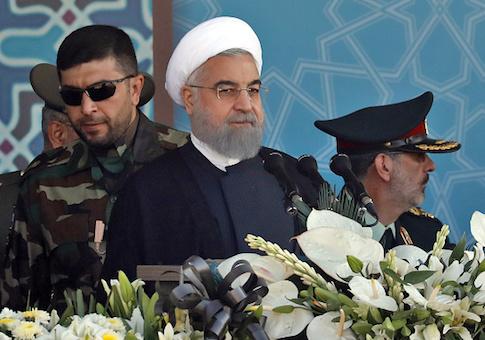 Iranian President Hassan Rouhani sits among senior army staff