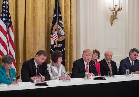 President Donald Trump is flanked by GOP senators to discuss health care