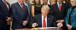 President Donald Trump signs an executive order on health insurance