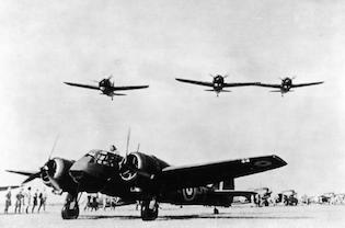 Three US Brewster Buffalo fighters fly over a British Bristol Blenheim bomber at an airfield in Singapore