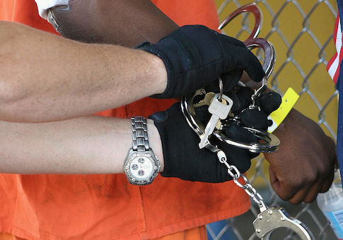 A corrections officer releases handcuffs