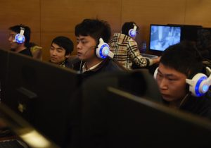 Men look at computers in an internet bar in Beijing