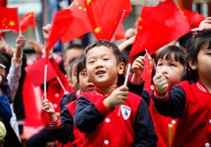 Children wave national flags as they sing revolutionary songs to celebrate the upcoming National Day at a kindergarten