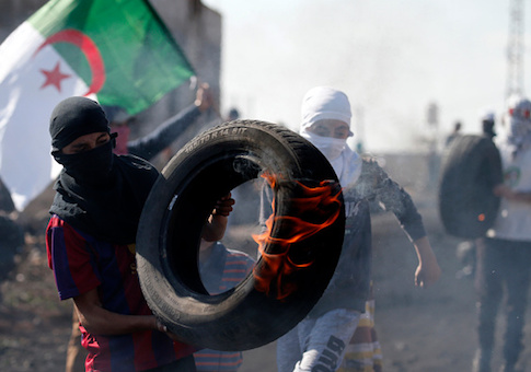 A Palestinian protester carries a burning tire during clashes with Israeli forces