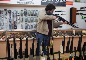 A customer sights a shotgun at a gun shop