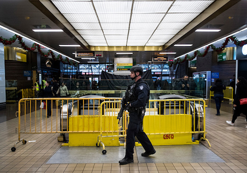A member of the New York City Police Department stands guard inside the New York Port Authority Bus Terminal after it reopened following an explosion
