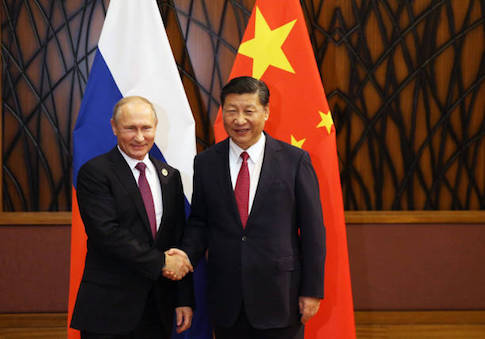Russian President Vladimir Putin shakes hands with China's President Xi Jinping