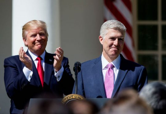U.S. Supreme Court Justice Judge Neil Gorsuch speaks as President Donald Trump looks on