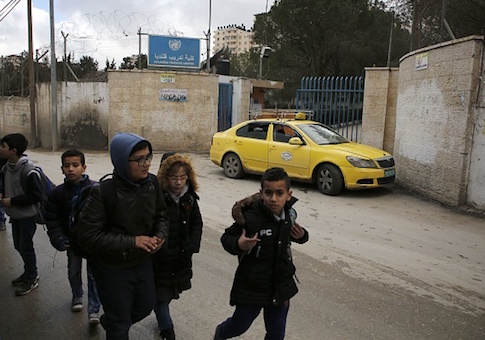 Palestinian boys walk past a United Nations' run school in the Qalandia refugee camp near Ramallah in the West Bank