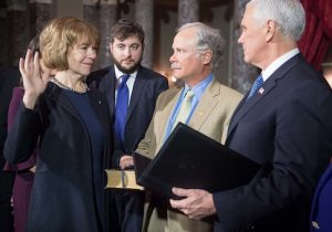 Sen. Tina Smith (L) is ceremonially sworn in by Vice President Mike Pence