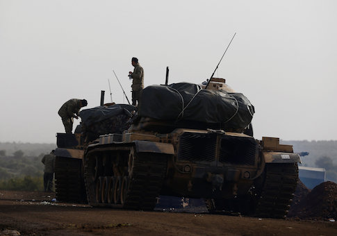Turkish soldiers stand on tanks in a village on the Turkish-Syrian border in Gaziantep province, Turkey