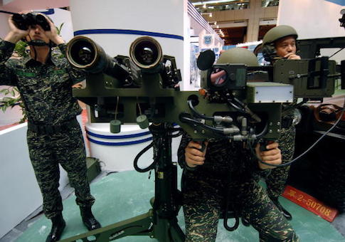 Three Taiwanese soldiers demonstrate a US-made dual mounted stinger missiles during the aerospace and defense technology exhibition at the World Trade Center in Taipei