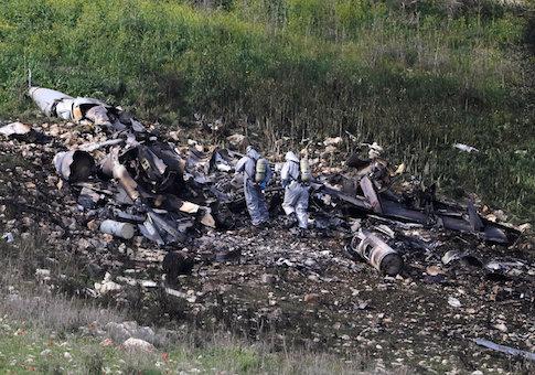 Israeli security forces examine the remains of an F-16 Israeli war plane near the Israeli village of Harduf, Israel