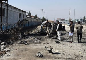 Afghan security personnel inspect the site of a Taliban car bomb attack in Kabul