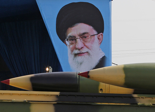 An Iranian military truck carries surface-to-air missiles past a portrait of Iran's Supreme Leader Ayatollah Ali Khamenei